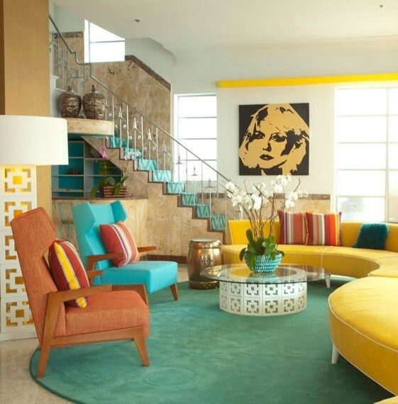 living room, grey round rug, glass table, yellow half round sofa, green chair, brown chair
