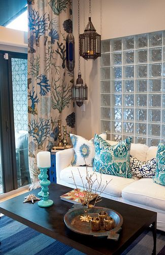 living room, striped blue rug, wooden coffee table, white sofa, blue patterned pillows, blue patterned curtain, moroccan pendant, white wall