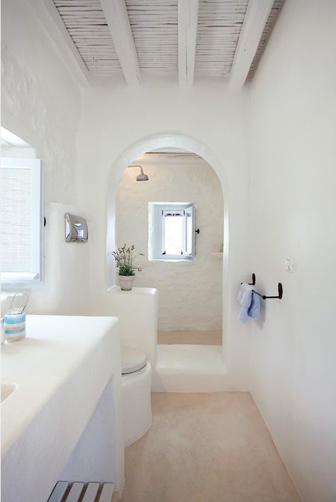long greek bathroom, white plastered wall, beige floor, curvy arch, white plastered vanity