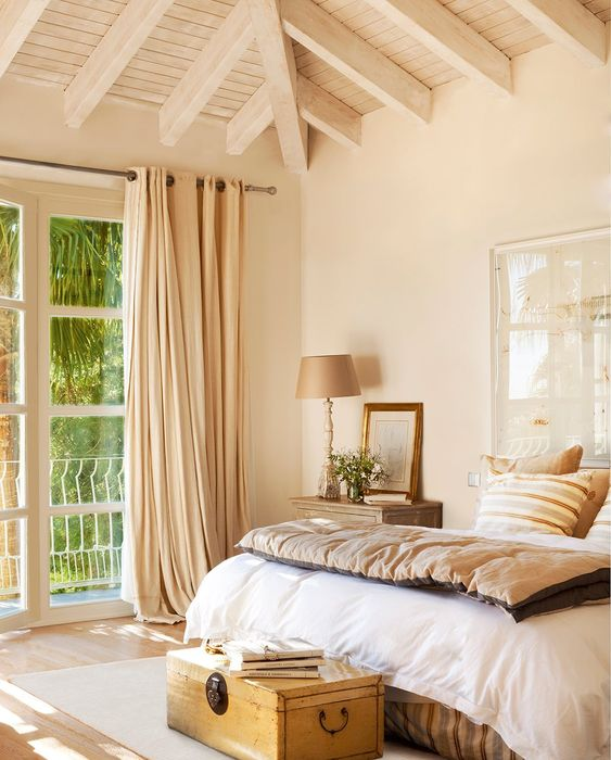 master bedroom, wooden floor, beige wall, wooden ceiling with beams, beige curtain, side table, wooden chest, white bedding, floor lamp