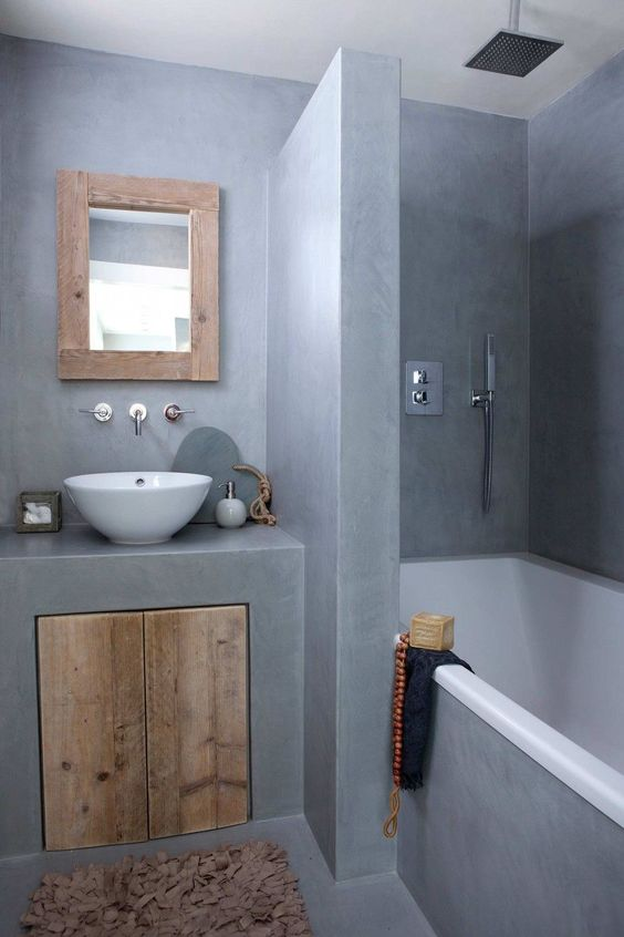 minimalist bathroom, cement surface, white tub inside, grey cement vanity with wooden doors, wooden framed mirror, white bowl sink