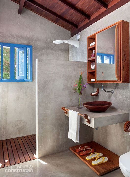 minimalist bathroom, grey surface on floor, wall, partition, floating vanity, brown earthen ware sink, floating cabinet with mirror, wooden floor, blue framed window