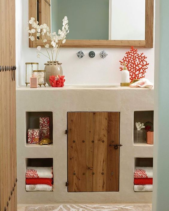 minimalist bathroom, white plaster vanity, built in shelves, wooden door, wooden framed mirror, white wall