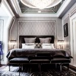 Mirrored Ceiling With Crystal Chandelier, Wooden Floor, Black Rug, Black Bedding With Headboard, Grey Wallpaper