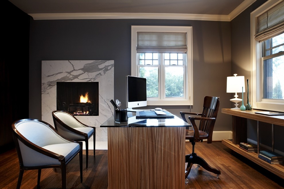 office guest chair windows marble fireplace wall gray walls gray shades wooden desk with black glass top wooden chairs wooden floor wooden console table white table lamp