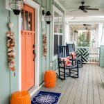 Orange Door, Orange Stool, Wooden Floor, Green Plank Wall, White Framed Windows, Sconce, Ceiling Fan, Two Rocking Chairs