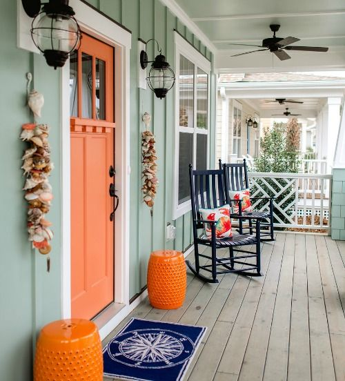 orange door, orange stool, wooden floor, green plank wall, white framed windows, sconce, ceiling fan, two rocking chairs