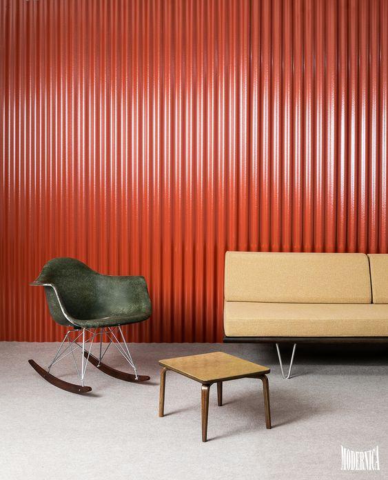 orange iron sheeting, grey floor, beige sofa, grey modern rocking chair, coffee table