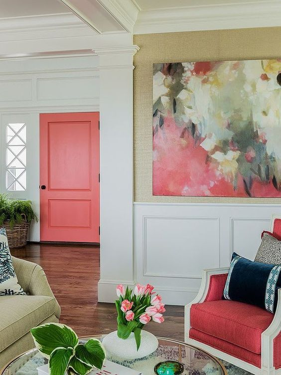 pink door, white wall, wainscoting, painting, green adn pink chairs