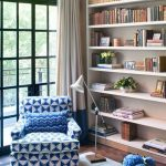 Reading Nook, Wooden Floor, White Wooden Shelves, Blue Patterned Couch, White Floor Lamp, Wooden Rug, White Curtain, Glass Window