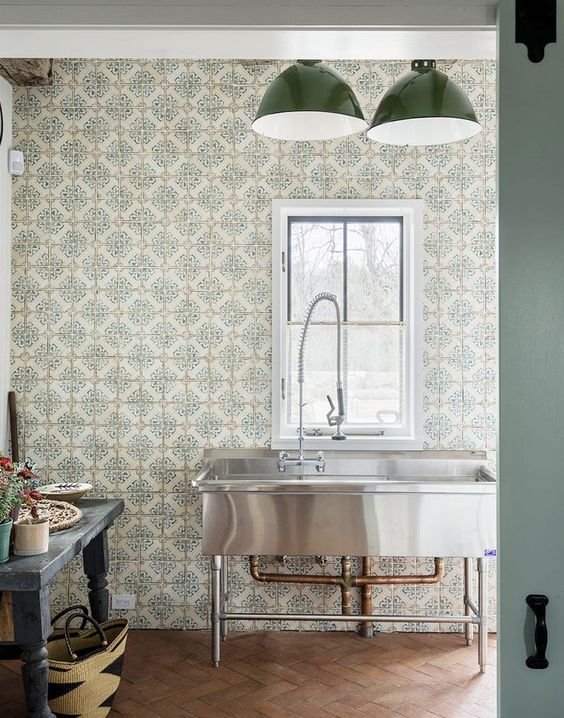 silver big rectangular sink, patterned wallpaper, green pendants, black wooden table, brown herringbone floor tiles