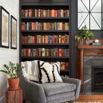 Small Corner Library With Black Built In Shelves, Grey Velvet Couch, Wooden Floor, White Rug, Grey Marble Fireplace With Wooden Frame, White Plank Wall