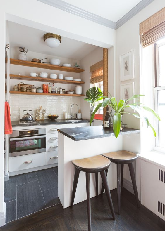 small kitchen, black floor tiles, white bottom cabinet and island, black marble top, white subway wall tiles, wooden floating shelves, black stools