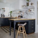 Small Kitchen, Grey Floor, White Wall, Black Bottom Cabinet, Wooden Kitchen Top, White Upper Cabinet, White Floating Shelves, Kitchen Grid, Wooden Stools
