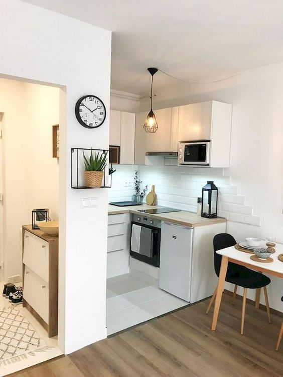 small kitchen, white floor, white bottom cornered cabinet, white cornered upper cabinet, wired pendant, wooden floor, white dining table, black chairs