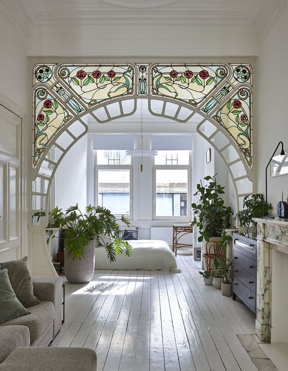 stained flowery patterned glass arch partition, white wooden floor, grey sofa, large window, fireplace, cabinet