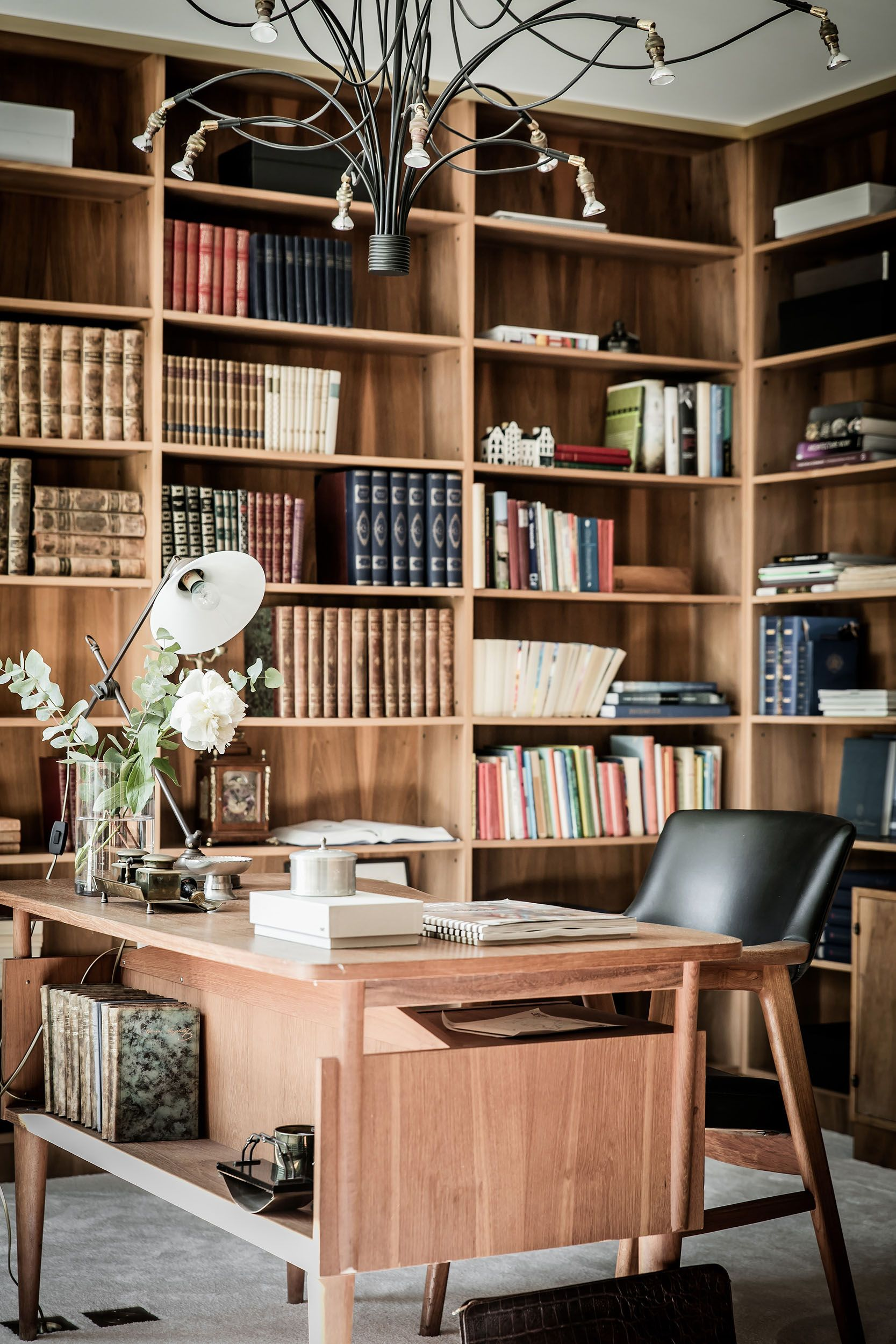 study room, seamless grey floor, wooden table, wooden chair with black leather seating, wooden built in shelves, chandelier,