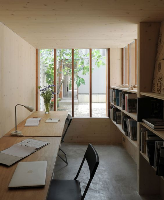study space, built in wooden floating shelves, grey seamless floor, wooden table, black chair, white table lamp