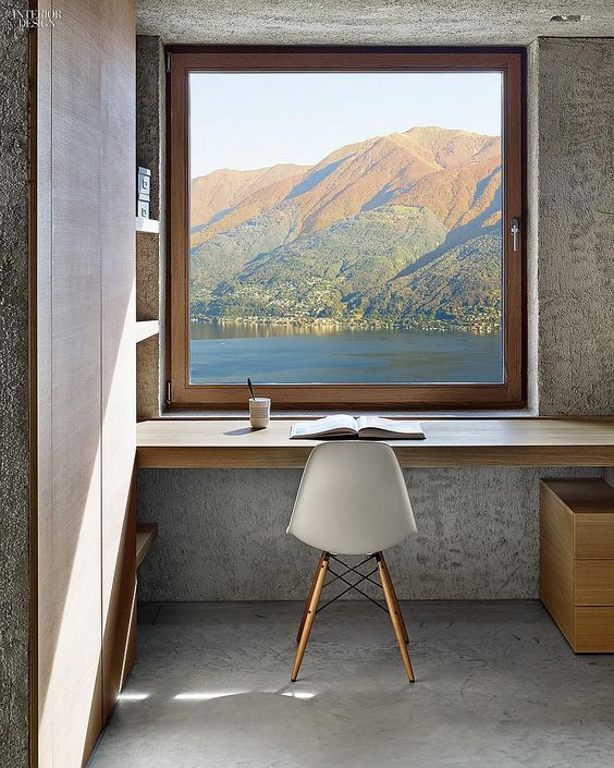 study space in front of the window, floating wooden table, grey seamless floor, built in shelves, window
