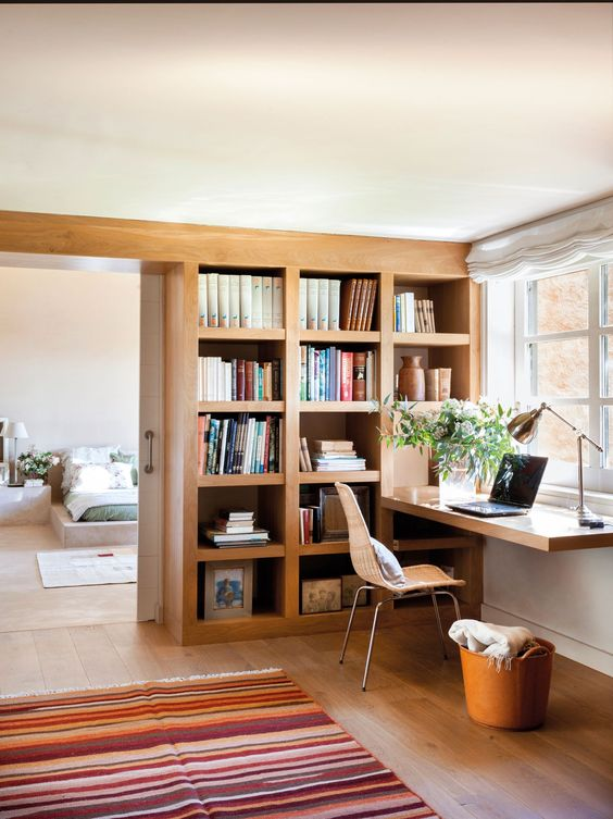 study space, wooden floor, floating wooden table, wooden built in bookshelves, rug, sliding door, bedroom,