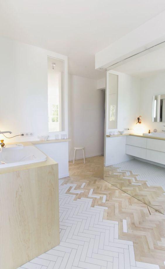 white and brown wooden herringbone floor tiles on the bathroom, white floating vanity, wooden vanity, white wall
