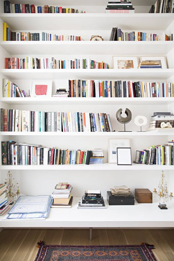 white bookshelves with longer part at the bottom, wooden floor, rug