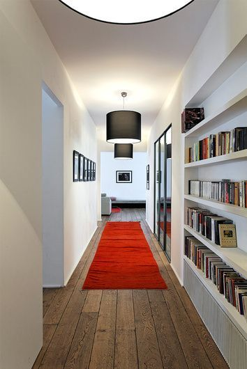 white built in bookshelves on the alley, wooden floor, red rug, black pendants