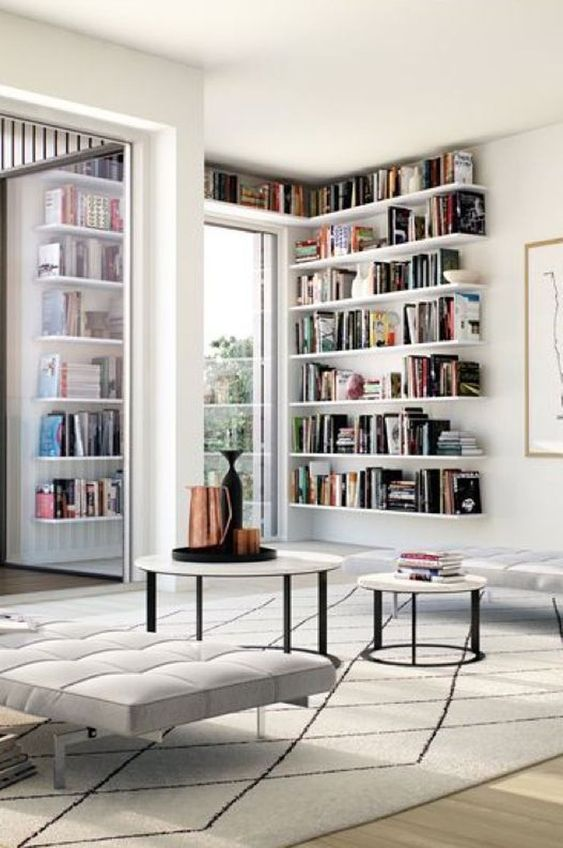 white corner bookshelves, wooden floor, white bench, round nesting table