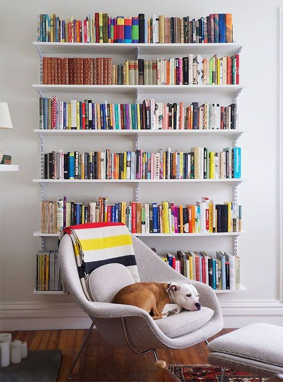 white floating bookshelves, wooden floor, white chair, white ottoman
