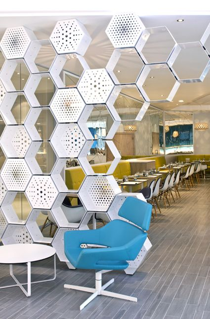 white hexagonal metal box as wall partition, blue chair, white coffee table