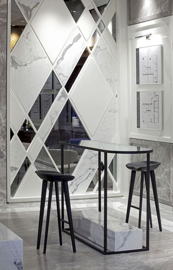 white marble wall with mirror blocks, marble floor, black high table with black stools