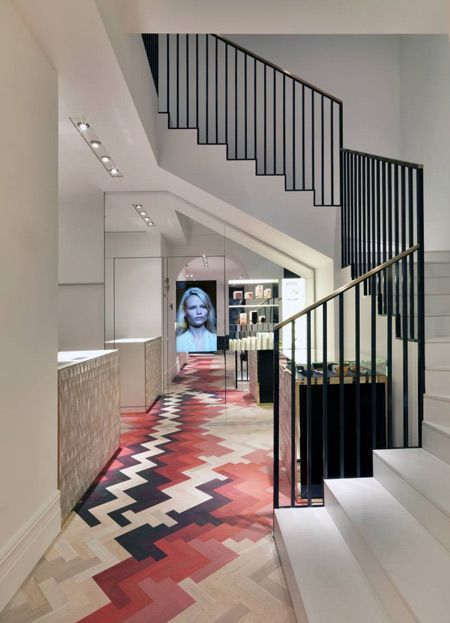 white pink black herringbone tiles one the floor, white wall, white stairs, black rail