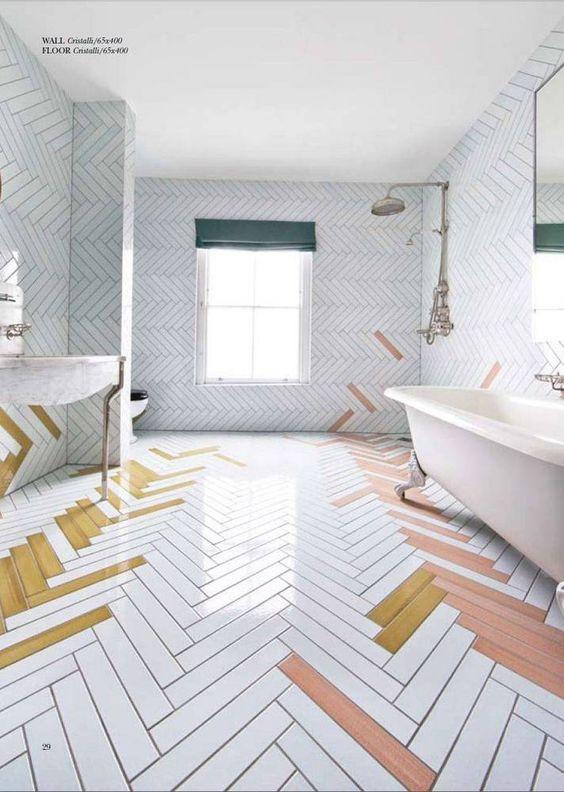 white pink, yellow herringbone tiles on the floor and wall, white ceiling, white tub, white vanity, mirror