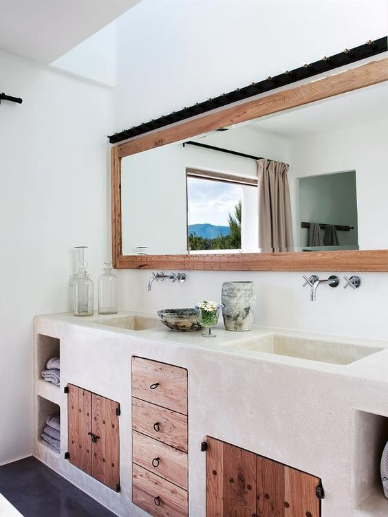 white plastered vanity, wooden drawers, wooden doors, built0in shelves, white wall, long mirror with wooden frame
