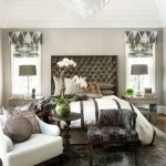 White Tray Ceiling With Crystal Chandelier, Wooden Floor, Dark Grey Rug, Tufted Headboard, White Chair, Dark Char, Grey Table Lamp, Gry Curtain