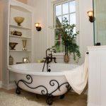 White Tub With Black Wrought Iron On The Bottom, Wooden Floor, White Wall, White Wooden Shelves,