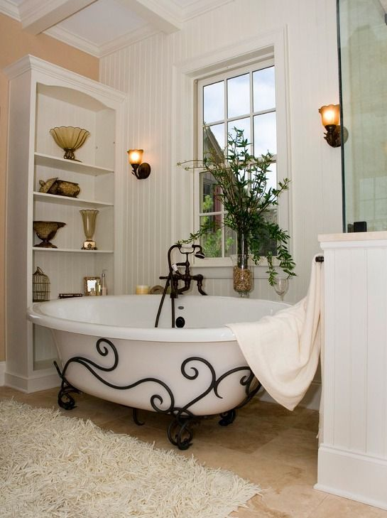 white tub with black wrought iron on the bottom, wooden floor, white wall, white wooden shelves,
