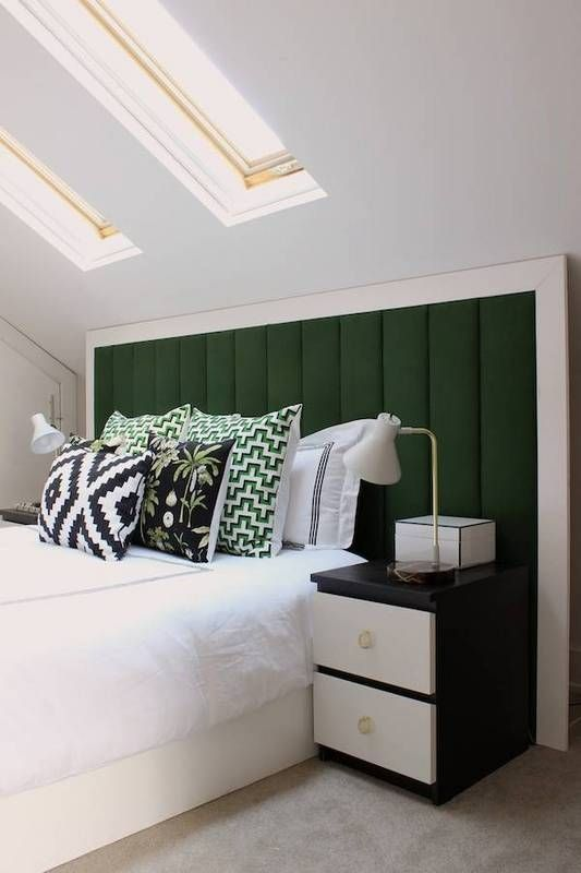 white wooden bed platform under the white sloping ceiling, ceiling window, green headboard, black side table with white drawer