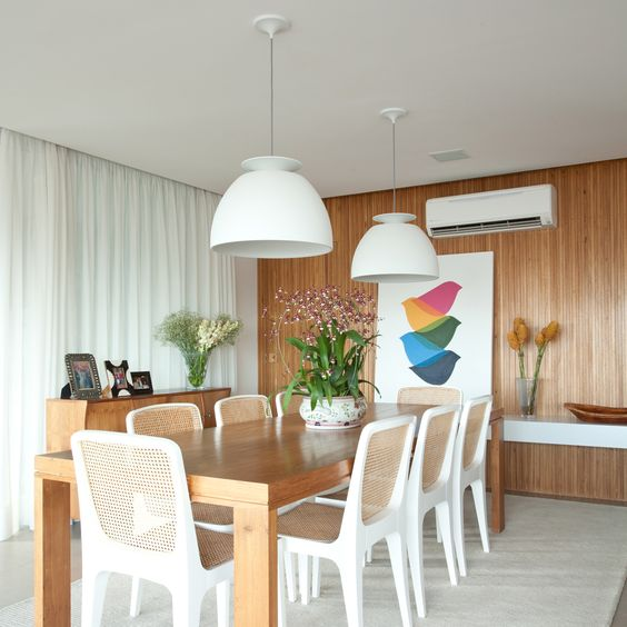 white wooden chairs with rattan back and seating, grey floor, wooden wall, white pendant, white curtain, wooden cabinet