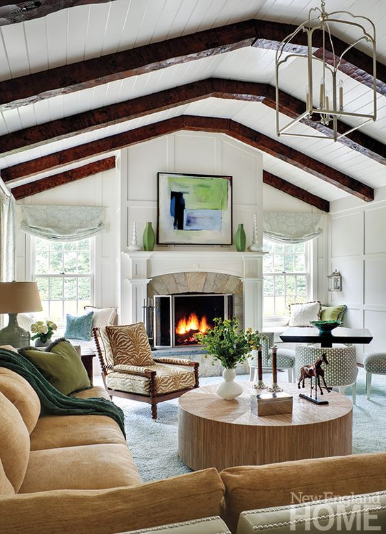 white wooden vaulted ceiling, dark wooden beams, white rug, brown sofa anc chairs, wooden round coffee table,