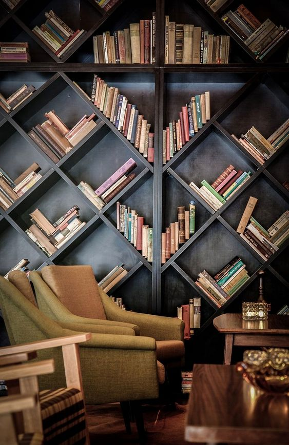 wooden book shelves with diamond shaped shelves, wooden table, green chairs, wooden floor