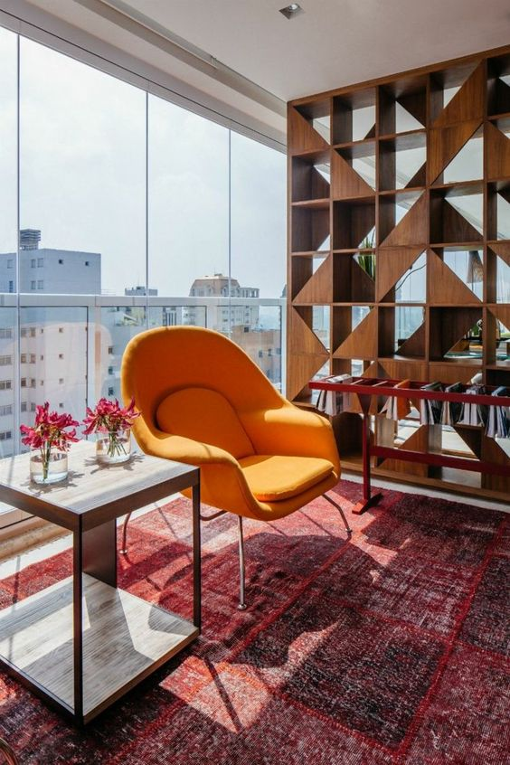 wooden book shelves with triangle patterns, orange chair, side table, red rug