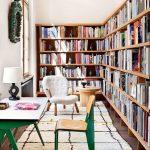 Wooden Bookshelves, Dark Grey Floor, White Rug, White Chair, Wooden Side Table, White Table With Green Legs, Brown Seating Chair With Green Legs
