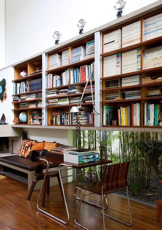 wooden floating bookshelves, wooden floor, black sofa, wooden table, wooden chair