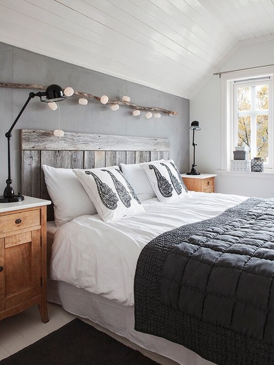 wooden palette headboard, white bedding, grey wall, white wooden ceiling, white wall, wooden side table, black table lamps