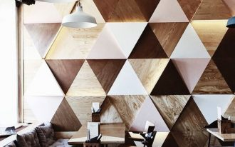 wooden triangle patterns on the wall with dark and light surface, wooden table, wooden chair, grey floor, white pendants