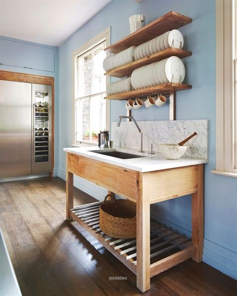 wooden vanity table, white top, indented sink, marble backsplash, blue wall, floating wooden shelves