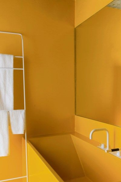 yellow seamless wall and sink, white faucet, mirror