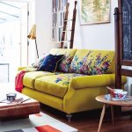 Yellow Sofa With Flowers Pattern, Wooden Floor, White Wall, White Built In Shelves, Golden Floor Lamp, Wooden Coffee Table, Wooden Side Table