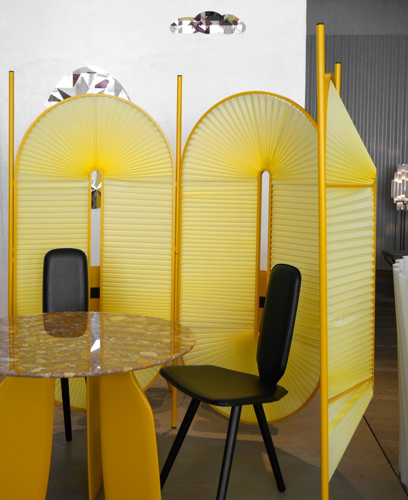 yellow unique divider with zigzag surface, black chair, marble top yellow table